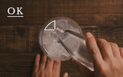 炭酸が抜けないように、<br>氷とグラスの隙間にトニックを注ぐ